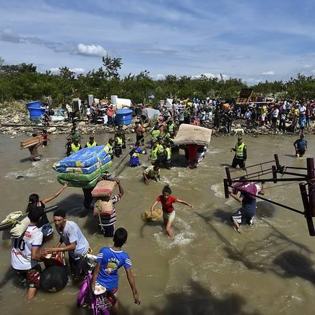 Colombianos deportados da Venezuela atravessam fronteira com seus pertences pelo Rio Táchira, em direção à cidade de Cúcuta, na Colômbia. Foto: LUIS ACOSTA / AFP
