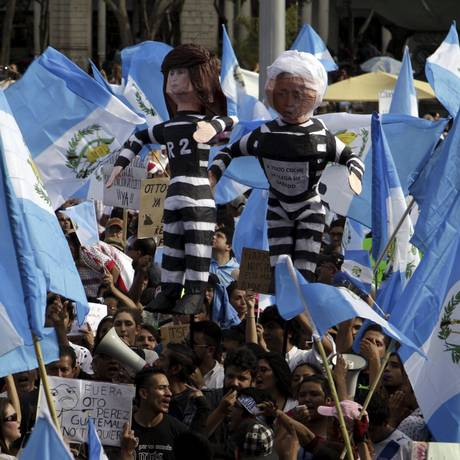 Manifestantes erguem bandeiras da Guatemala e efígies representando o presidente Otto Pérez Molina e a ex-vice-presidente Roxana Baldetti durante um protesto Foto: STRINGER / REUTERS
