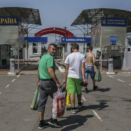 Após compras em Velke Slemence, na Eslováquia, homens se dirigem ao portão para cruzar a fronteira Foto: MAURICIO LIMA / NYT