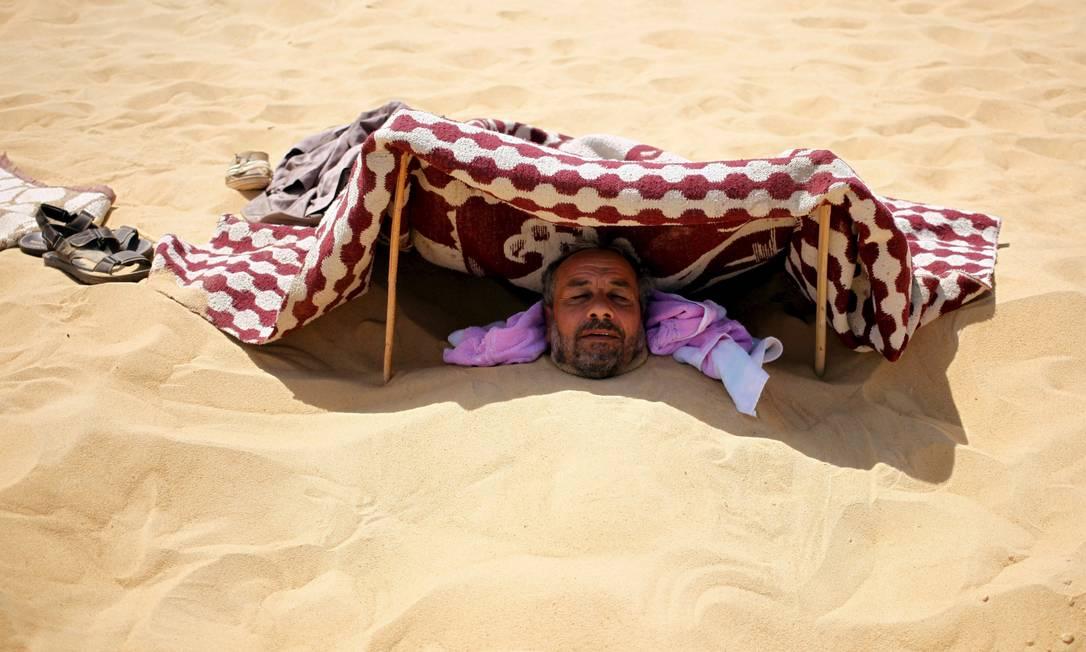 Paciente enterrado nas areias escaldantes do deserto, em Siwa, no Egito, onde ocorre tratamento que promete a cura de reumatismo, impotencia e infertilidade, entre outras doenças. Antes de serem cobertos de areia até o pescoço, os pacientes relaxam à sombra de tendas montadas, onde depois retornam para tomarem chá de hortelã ASMAA WAGUIH / REUTERS