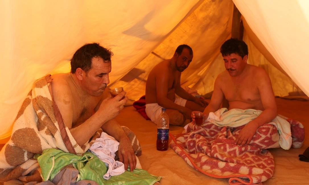 Pacientes tomam chá de hortelã depois de serem desenterrados das areias escaldantes do deserto, em Siwa, no Egito, onde ocorre tratamento que promete a cura de reumatismo, impotencia e infertilidade, entre outras doenças ASMAA WAGUIH / REUTERS