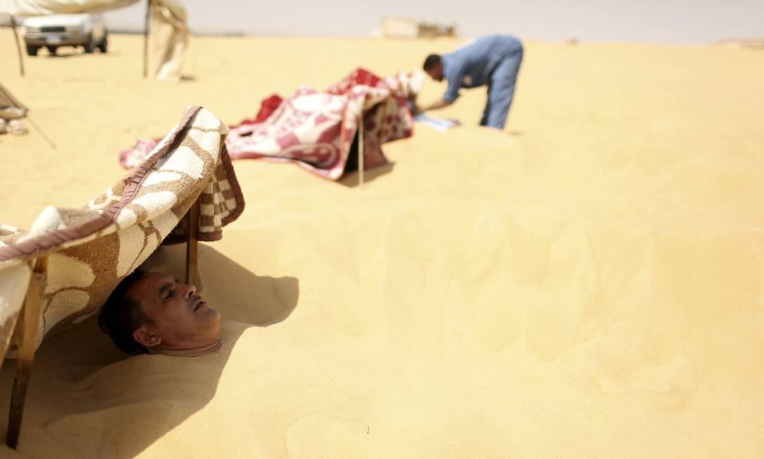Funcionário ajuda paciente enterrado nas areias escaldantes do deserto, em Siwa, no Egito, onde ocorre tratamento que promete a cura de reumatismo, impotencia e infertilidade, entre outras doenças. Antes de serem cobertos de areia até o pescoço, os pacientes relaxam à sombra de tendas montadas, onde depois retornam para tomarem chá de hortelã ASMAA WAGUIH / REUTERS