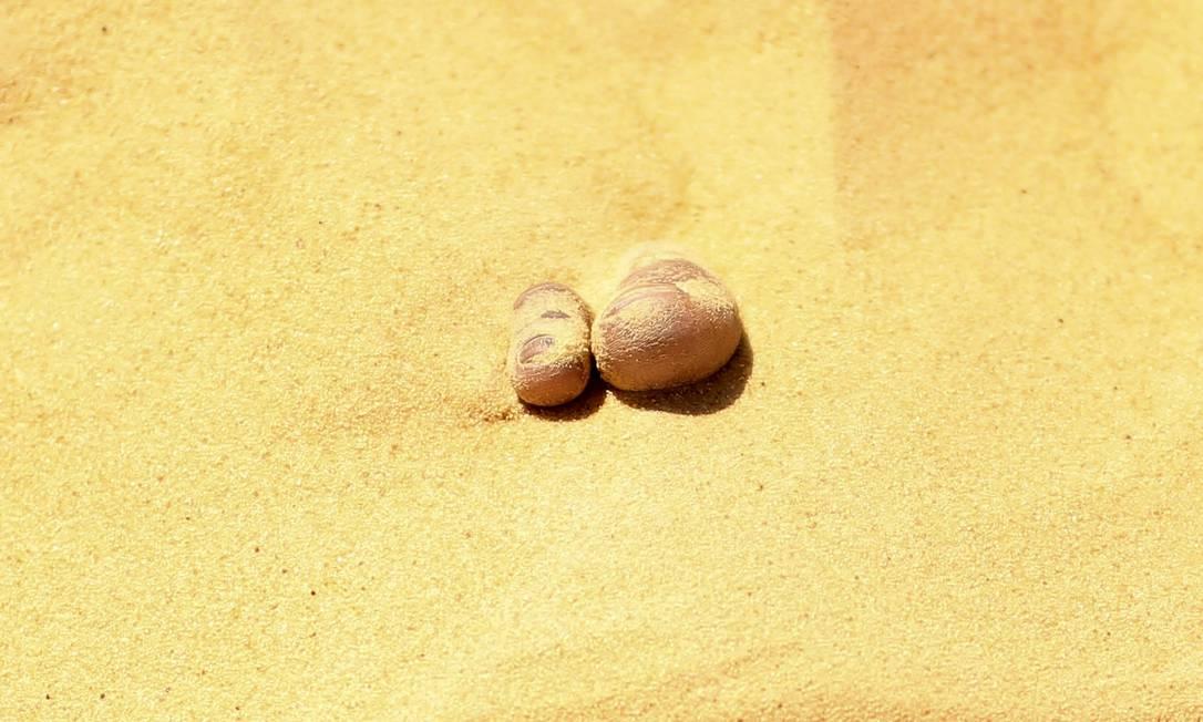 Dedões de um paciente enterrado nas areias escaldantes do deserto, em Siwa, no Egito, onde ocorre tratamento que promete a cura de reumatismo, impotencia e infertilidade, entre outras doenças. Antes de serem cobertos de areia até o pescoço, os pacientes relaxam à sombra de tendas montadas, onde depois retornam para tomarem chá de hortelã ASMAA WAGUIH / REUTERS