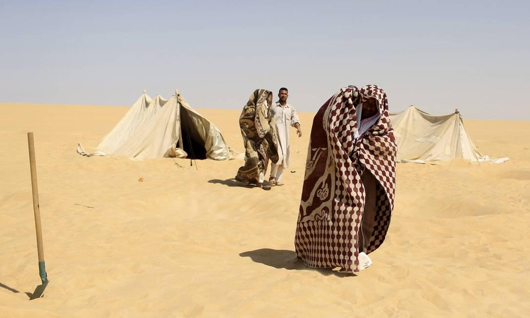 Funcionário ajuda paciente que será enterrado nas areias escaldantes do deserto, em Siwa, no Egito, onde ocorre tratamento que promete a cura de reumatismo, impotencia e infertilidade, entre outras doenças. Antes de serem cobertos de areia até o pescoço, os pacientes relaxam à sombra de tendas montadas, onde depois retornam para tomarem chá de hortelã ASMAA WAGUIH / REUTERS