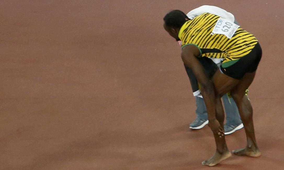 Usain Bolt leva a mão ao tornozelo após ser atingido por um cinegrafista a bordo de um veiculo Segway usado pelo profissional da tv. KIM KYUNG-HOON / REUTERS