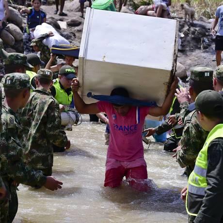 Colombianos levam seus pertencem pela fronteira com a Venezuela após serem deportados Foto: LUIS ACOSTA / AFP