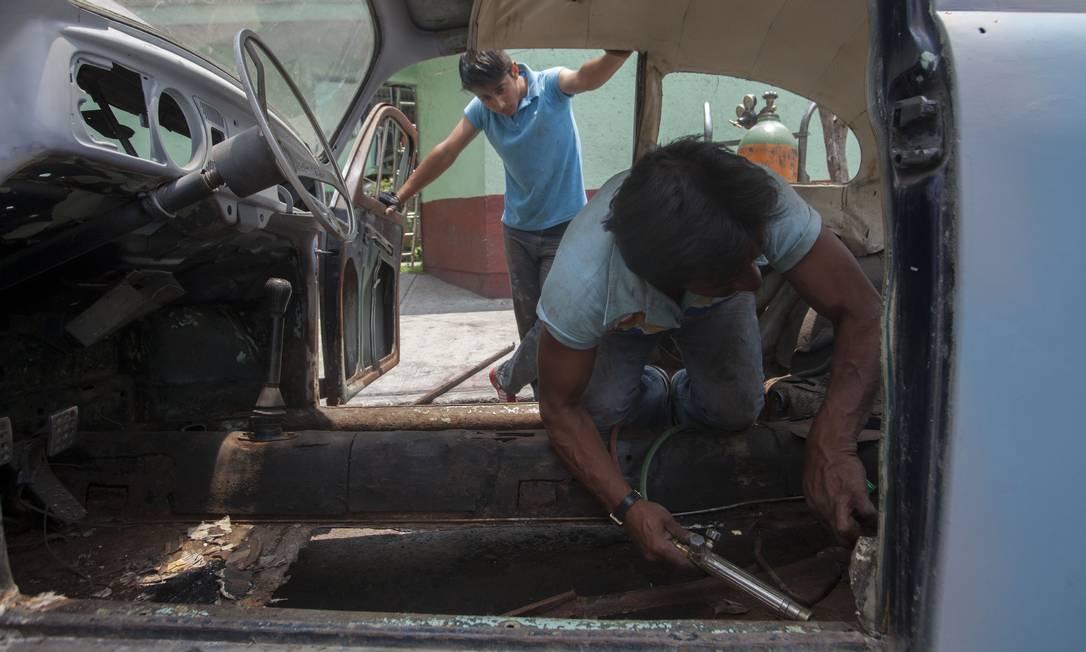 """Armando Garcia, esquerda, observa seu pai, Armando Aguilar, desmontando o carro de cliente que será reformado. A mania de manter, transformar ou reformar o carro popular da volks é conhecido no México como """"vochomania"""" Sofia Jaramillo / AP"""