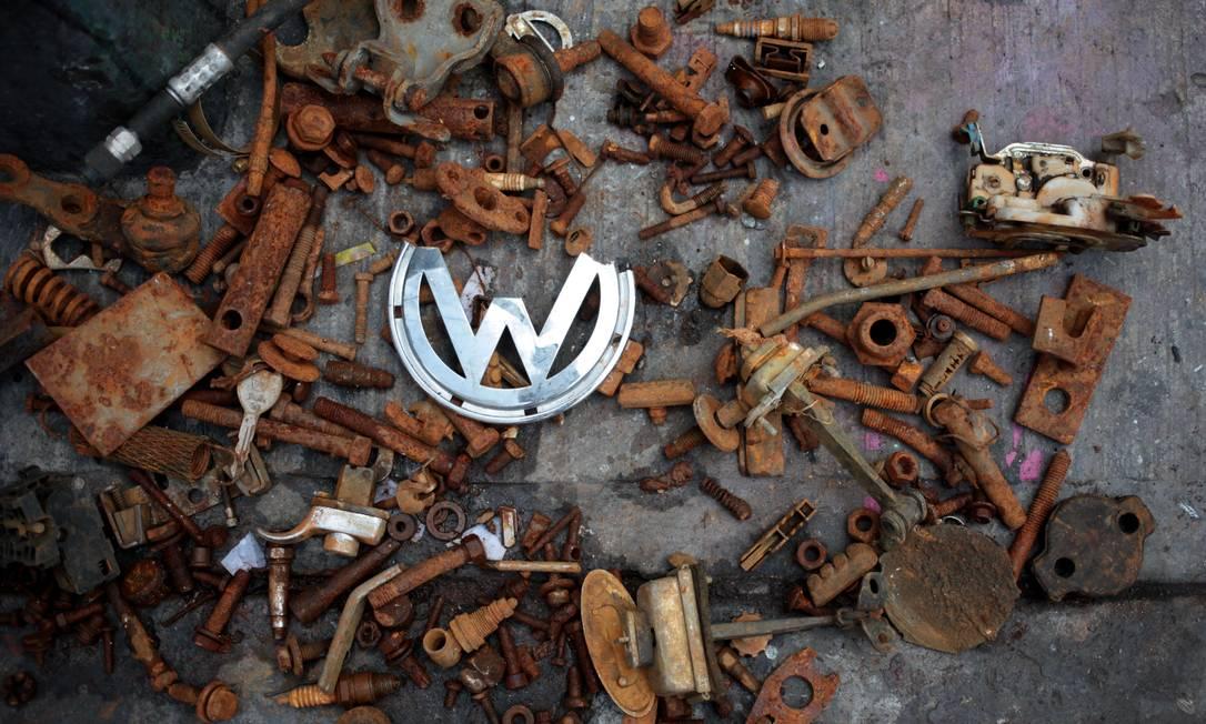 """Peças e partes de um fusca, incluindo o icônico símbolo da Volks, enferrujam em um ferro-velho na cidade do México. O clássico """"besouro"""" da Volkswagen foi produzido até 2003, em Puebla e é conhecido no México como """"vocho"""" Sofia Jaramillo / AP"""