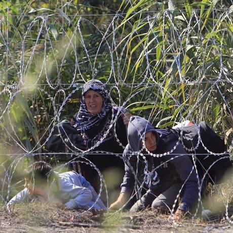 Família de refugiados sírios, no lado sérvio da fronteira com a Hungria, deitam na terra atrás de uma cerca de arame, perto da cidade húngara de Röszke Foto: BERNADETT SZABO / REUTERS