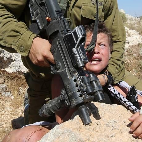 Com braço quebrado, menino palestino foi retido por soldado israelense que segurava uma metralhadora Foto: ABBAS MOMANI / AFP