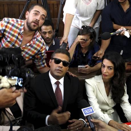 Mohamed Fahmy (centro), Baher Mohamed (à esq.) e a advogada Amal Clooney falam à imprensa antes do anúncio do veredicto em uma corte no Cairo Foto: ASMAA WAGUIH / REUTERS