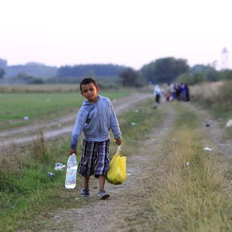 Uma criança síria caminha ao longo de uma estrada depois de cruzar para a Hungria a partir da fronteira com a Sérvia, perto da cidade húngara de Röszke Foto: BERNADETT SZABO / REUTERS