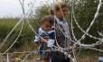 Imigrante síria carrega criança atrás de cerca na fronteira entre Sérvia e HUngrua