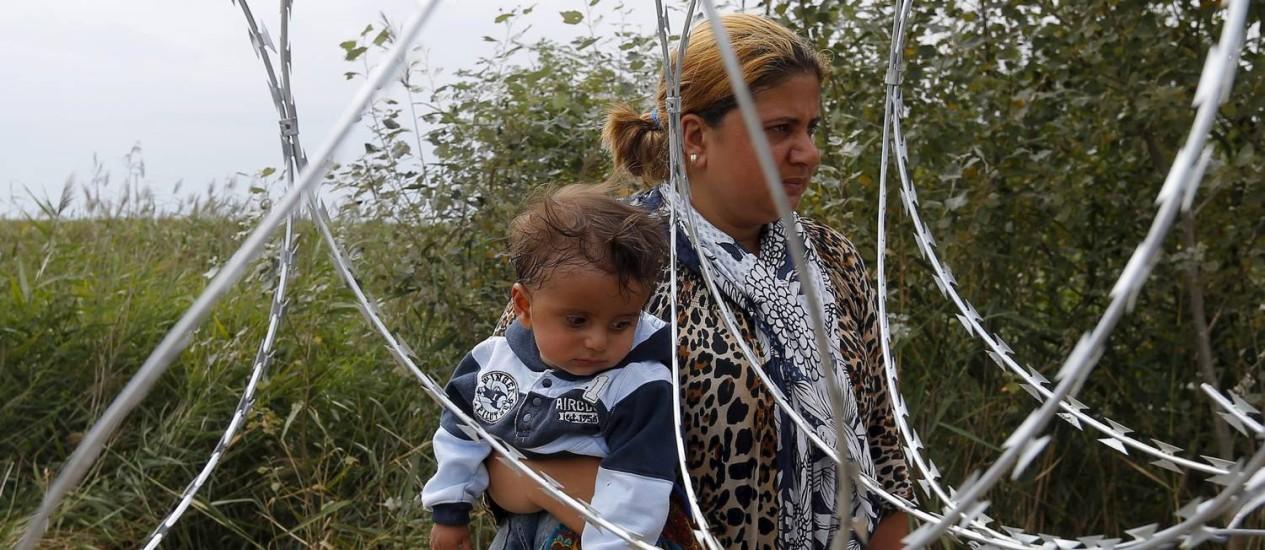 Imigrante síria carrega criança atrás de cerca na fronteira entre Sérvia e HUngrua Foto: LASZLO BALOGH / REUTERS