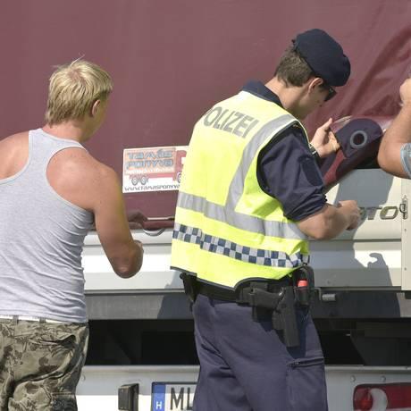 Policial austríaco inspeciona caminhão na fronteira com a Hungria na cidade de Nickelsdorf Foto: Hans Punz / AP