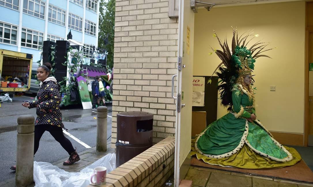 Passista da The London School of Samba se protege da chuva aguardando o início do segundo dia de desfile do Carnaval de Notting Hill, zona oeste de Londres LEON NEAL / AFP