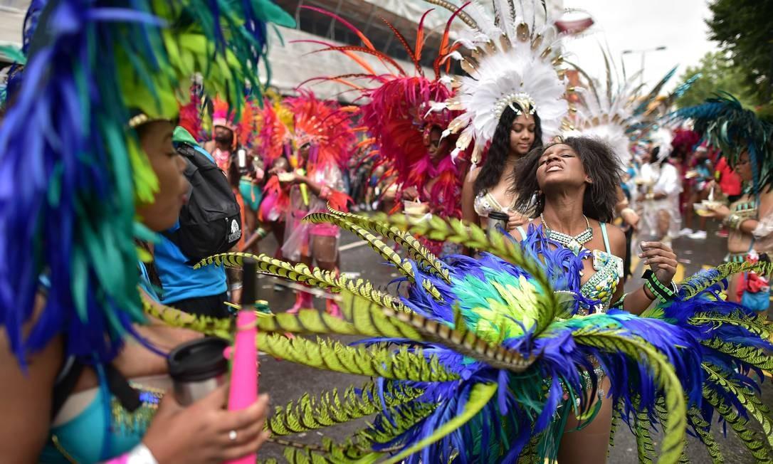 Passistas no segundo dia de desfile do Carnaval de Notting Hill, zona oeste de Londres. O evento existe desde 1960 e é considerado a maior manifestação popular de rua da Europa, e celebra a influencia da imigraçao caribenha na região LEON NEAL / AFP