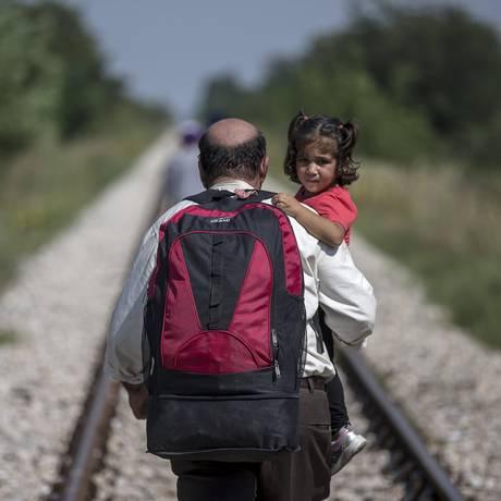 Um imigrante, tentando chegar à Hungria, carrega uma criança em uma estrada perto da vila de Horgos, na Sérvia, na fronteira com a Hungria Foto: MARKO DJURICA / REUTERS