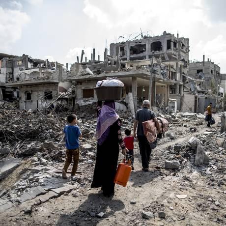 Familia palestina retorna para os destroços de sua casa em Gaza, após um ataque de Israel Foto: MARCO LONGARI / AFP