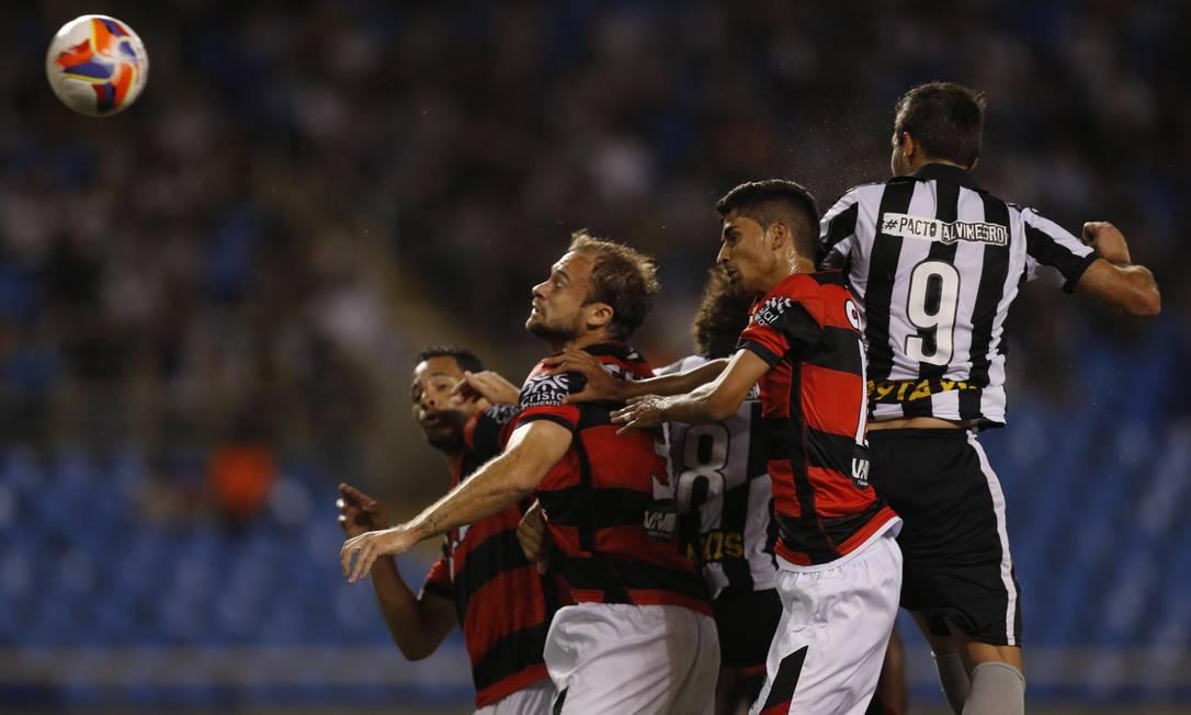 O uruguaio Navarro disputa a bola com a zaga do Atlético-GO Alexandre Cassiano / Agência O Globo