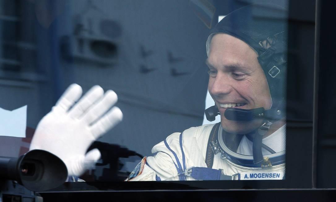 O austronauta dinamarques Andreas Mogensen acena da janela do transporte para a base de lançameto do foguete Soyuz FG, no cosmódromo de Baikonur no Cazaquistão DMITRY LOVETSKY / AFP