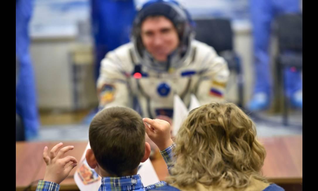 O cosmonauta russo Sergei Volkov se comunica com familiares através de um vidro enquanto aguarda o embarque no foguete Soyuz que levará ele e outros dois colegas à Estação Espacial Internaciona (ISS) KIRILL KUDRYAVTSEV / AFP