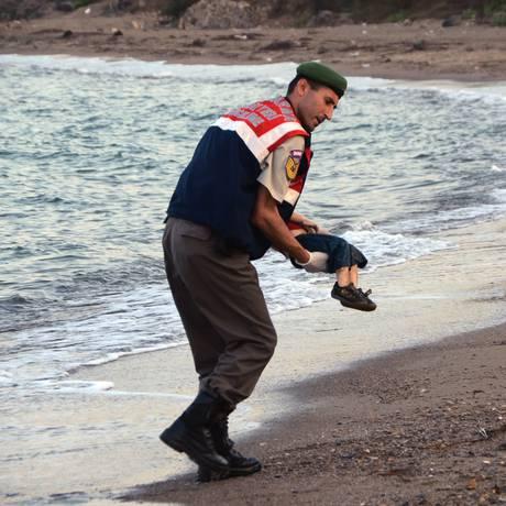 Com expressão sombria, membro da guarda costeira carrega o pequeno corpo da criança Foto: DHA / AP