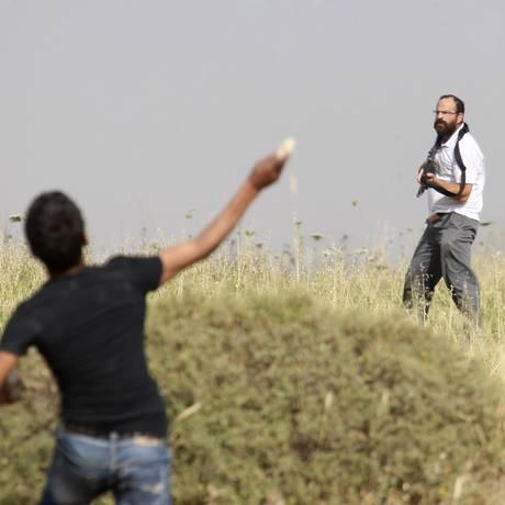 Jovem palestino joga pedra em homem judeu armado durante confrontos na cidade de Assira al-Kibliya, na Palestina. Foto: Nasser Ishtayeh / AP