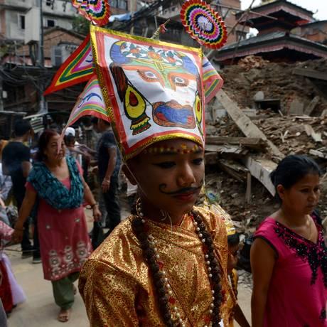Menino vestido em um traje tradicional nepalês durante procissão em Katmandu passa em frente a casa destruída Foto: PRAKASH MATHEMA / AFP