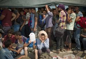 GRÉCIA. Em fila e sentados, protegendo-se como podem do sol escaldante, refugiados e imigrantes aguardam para fazer os procedimentos de entrada no porto da ilha grega de Lesbos: a Organização Internacional para Imigração divulgou que cerca de 2 mil pessoas por dia estão entrando em Grécia, Macedônia e Sérvia, podendo chegar a 3 mil Foto: DIMITRIS MICHALAKIS / DIMITRIS MICHALAKIS/REUTERS