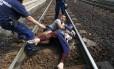 Policiais tentam retirar um homem com sua mulher e filho de trilho de trem na cidade húngara de Biscke