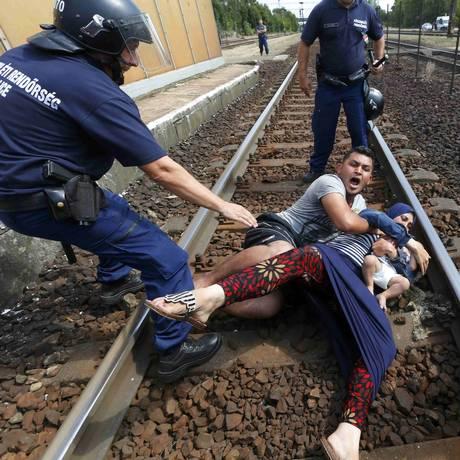 Policiais tentam retirar um homem com sua mulher e filho de trilho de trem na cidade húngara de Biscke Foto: LASZLO BALOGH / REUTERS