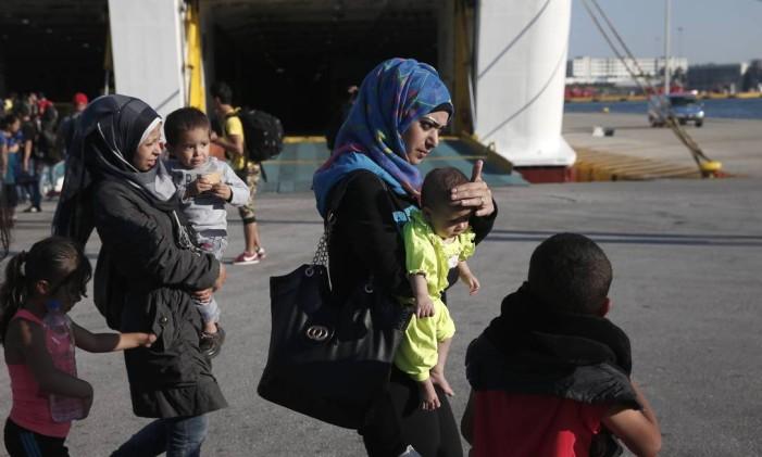 Imigrantes sírios desembarcam em porto perto de Atenas, na Grécia, depois de terem passado pela Turquia Foto: Petros Giannakouris / AP