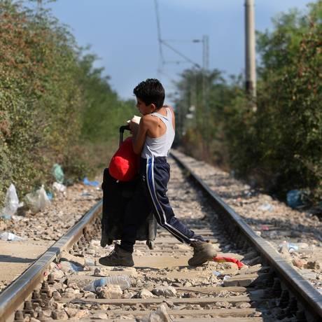Uma criança imigrante atravessa a fronteira entre Grécia e Macedônio perto do vilage de Idomeni, norte da Grécia Foto: SAKIS MITROLIDIS / AFP