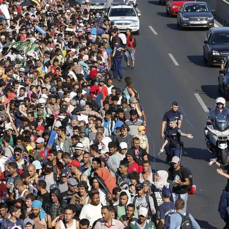 Centenas de imigrantes saem de Budapeste em viagem a pé até a Áustria Foto: Frank Augstein / AP