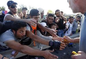 Imigrantes recebem comida na caminhada de Budapeste até a Áustria Foto: Frank Augstein / AP