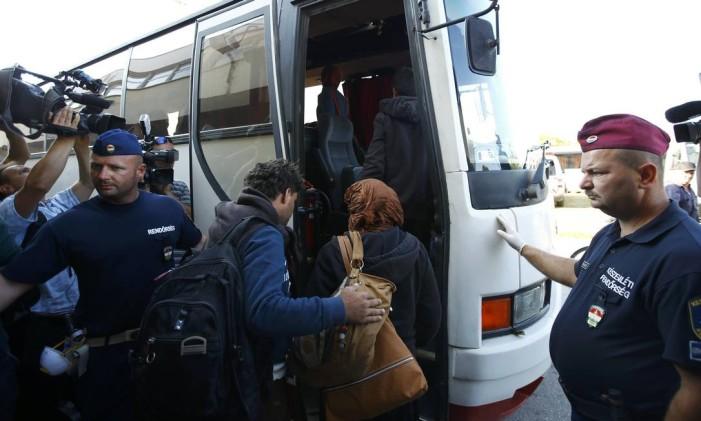 Policiais escoltam migrantes saindo de centro de refugiados Foto: LEONHARD FOEGER / REUTERS