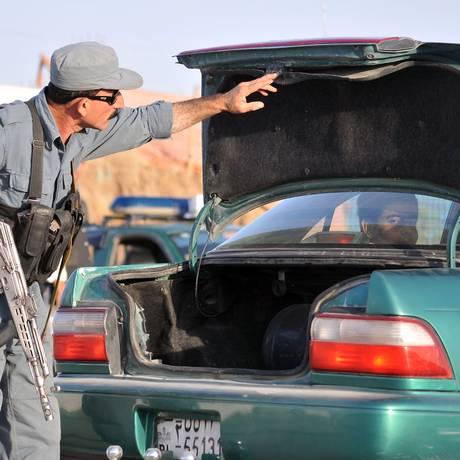 Um policial afegão verifica o porta-malas de um carro em um posto de controle em Balkh: ao menos 13 civis foram mortos no sábado na província Foto: Mustafa Najafizada / AP
