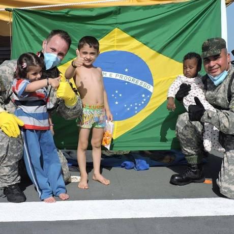 Membros da Marinha posam com crianças resgatadas de barco no Mediterrâneo Foto: Divulgação/Marinha do Brasil
