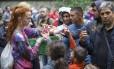 Acolhimento. Jovens distribuem frutas a refugiados em Berlim. Enquanto governos ainda discutem como resolver a crise migratória, pessoas se coordenam através da internet para oferecer hospedagem, alimentor e roupas a i