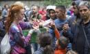Acolhimento. Jovens distribuem frutas a refugiados em Berlim. Enquanto governos ainda discutem como resolver a crise migratória, pessoas se coordenam através da internet para oferecer hospedagem, alimentor e roupas a i Foto: HANNIBAL HANSCHKE / REUTERS