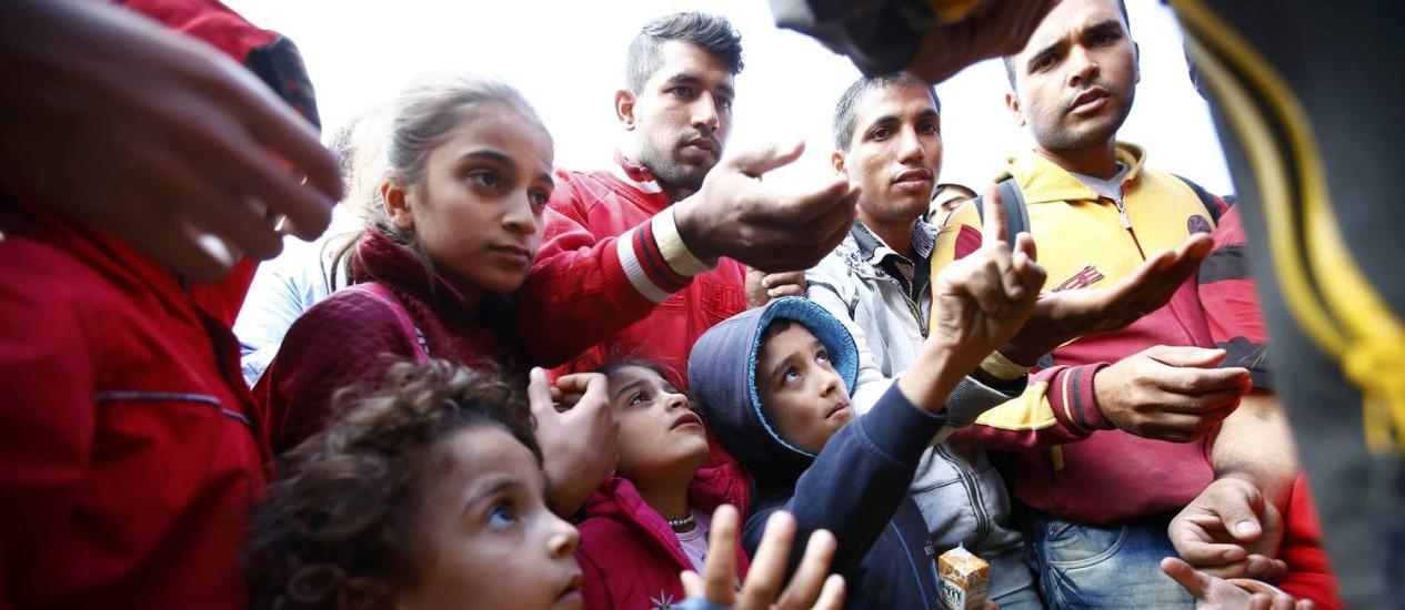 Imigrantes recebem comida ao chegar na estação ferroviária em Hegyeshalom, na Hungria Foto: LEONHARD FOEGER / REUTERS