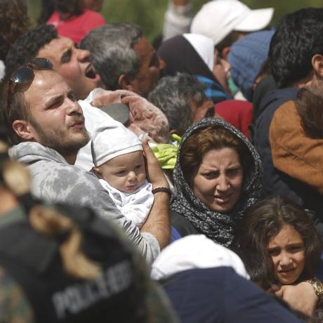 Imigrantes carregam seus filhos ao tentar embarcar em trem na fronteira da Grécia com Macedônia Foto: STOYAN NENOV / REUTERS