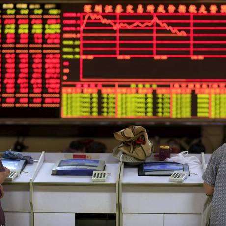 Clientes em corretora de Xangai nesta segunda-feira Foto: Reuters