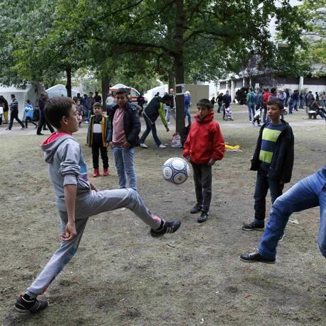 Matando o tempo: imigrantes jogam bola do lado de fora da agência em Berlim Foto: FABRIZIO BENSCH / REUTERS