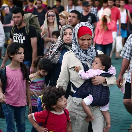 Mulher carrega seu bebê ao chegar no porto grego de Piraeus, perto de Atenas, depois de passar pela ilha de Lesbos Foto: LOUISA GOULIAMAKI / AFP