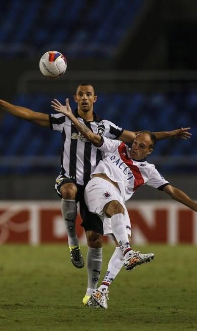 Roger Carvalho, do Botafogo, divide a bola com um jogador do Paraná Alexandre Cassiano / Agência O Globo