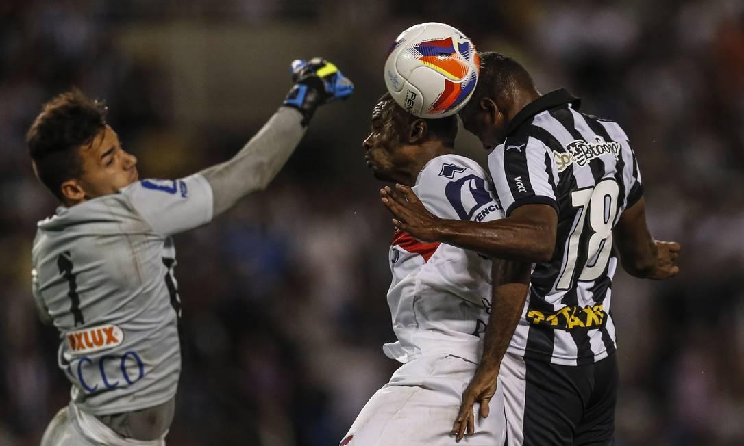 Sassá, herói da vitória, disputa a bola com o goleiro e zagueiro do Paraná Alexandre Cassiano / Agência O Globo