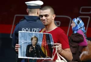 Imigrante segura foto da chanceler alemã, Angela Merkel, depois de chegar à principal estação de trem de Munique Foto: MICHAEL DALDER / REUTERS