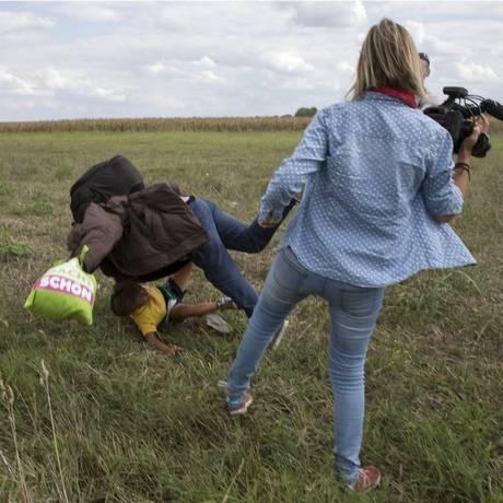 Petra Laszlo foi filmada chutando uma criança refugiada e dando uma rasteira em outro imigrante que tentavam entrar na Hungria a partir da fronteira com a Sérvia Foto: MARKO DJURICA / REUTERS